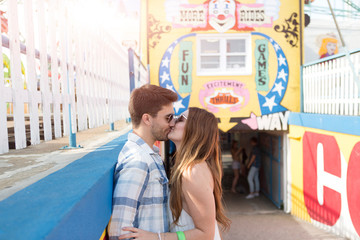 Young couple kissing in amusement park