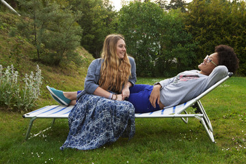 Teenage girls relaxing on lawn chair