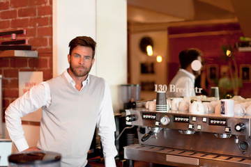 Portrait of mature man behind counter in cafe