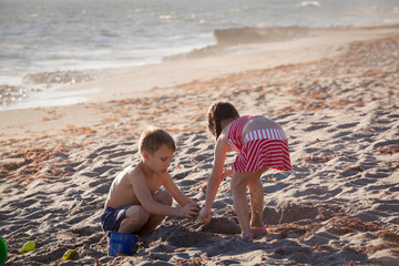 Boy and sister playing with sand on beach, Blowing Rocks Preserve, Jupiter Island, Florida, USA