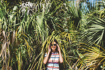 Woman hiding among palm fronds, Bonita Springs, Florida