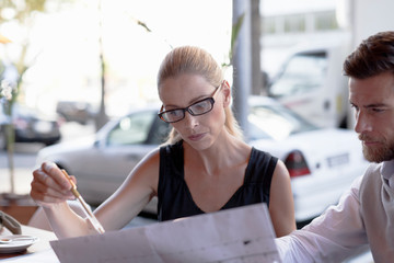 Mature man and woman, sitting outside cafe, looking at documents