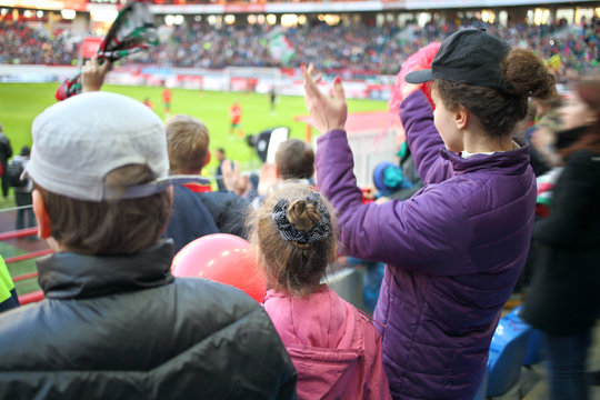 Woman, girl and boy standing applause among fans at a sports stadium, the view from the back