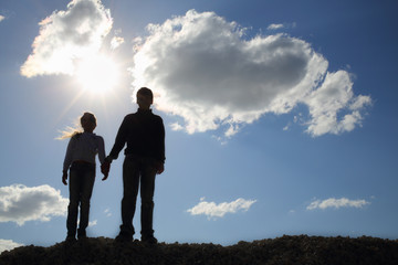 Brother and sister holding hands while standing on a hill against the sky