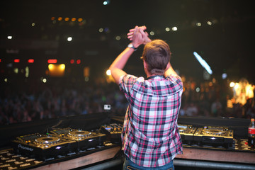DJ applauding public and spinning the decks at the Trancemission in Stadium Live, view from the back