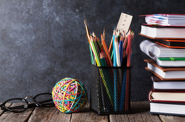 Notepads, supplies and glasses in front of chalk board