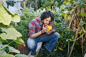 Caucasian man smelling peppers in garden