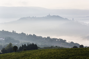 Morning fog over hills and town, Todi, Umbria, Italy