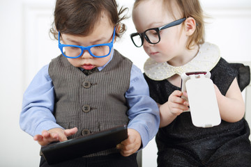 Little girl in glasses and black dress with mobile phone next to serious boy with tablet computer