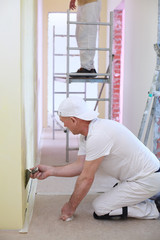 Finisher sitting on the floor inflicts the plaster on the wall using a pallet
