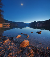Night in Alpsee lake in Germany. Beautiful landscape with lake, mountains, forest, stars, full moon, blue sky and stones in water. Panoramic photo. Spring
