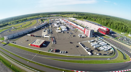 Trucks and cars parked on stadium Moscow Raceway. Aerial view (Photo with noise from action camera)