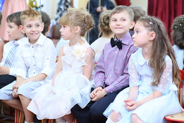 Five elegant small children sit on a chair in the hall at the feast in the kindergarten