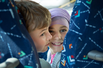 Two children are sitting in bus and turning back.