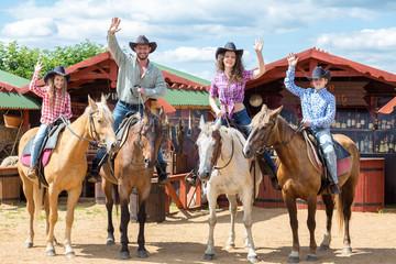 happy cowboy family of four on horsebacks waving their hands