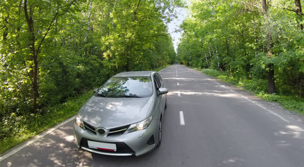Car travels by road among trees with green foliage in forest at summer day. Aerial view