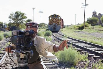 African American man with film camera near railroad tracks
