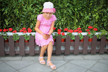 Little girl reading a flyer near the green fences and red geraniums
