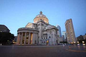 Mary Baker Eddy Library and Christian Science Mother Church near pond at autumn evening.
