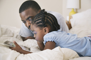 African American father and daughter using digital tablet on bed