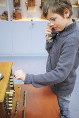 Boy with handset stands about old telephone commutator in the museum