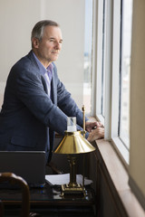 Caucasian businessman looking out office window