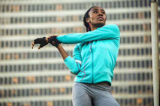 Black runner stretching near highrise building
