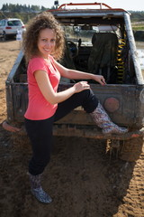 Beautiful woman is standing next to off-road vehicle.