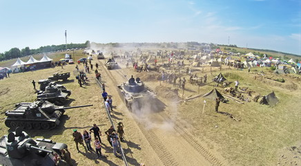 Tanks ride near military camp with many people during reconstruction Battlefield at Second World War. Aerial view (Photo with noise from action camera)