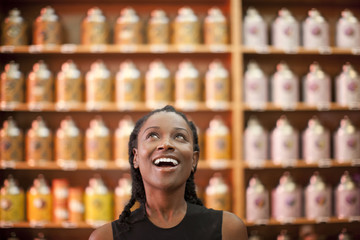 Smiling Black woman looking up in shop