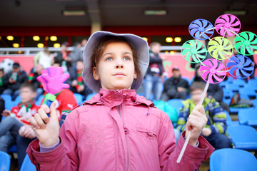 Girl in a pink jacket and panama hat with ratchet and wind spinner in the hands at stadium