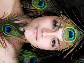 Woman surrounded by peacock feathers