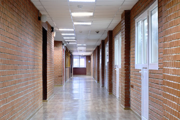 Interior of a long room with masonry and plastic windows