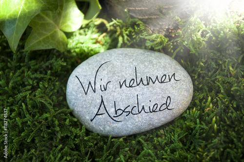 Stein auf Moos mit Efeu und Trauerspruch Wir nehmen Abschied ...
