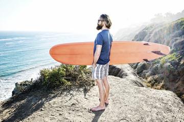 Caucasian man holding surfboard on coastal hilltop