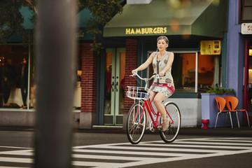 Older Caucasian woman riding bicycle in crosswalk