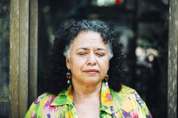 Hispanic woman standing with eyes closed outdoors