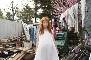 Caucasian girl standing in dilapidated backyard