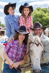 cowboy family of four with a horse closeup