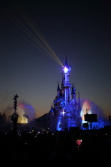 People watch the evening show with magic illumination about castle at Disneyland.