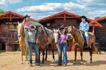 cowboy family of four with horses