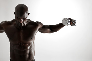 Muscular african fitness model working out with dumbbells