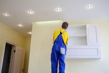 male furniture adjuster in uniform hang wall drawer