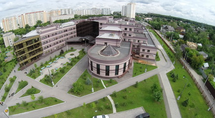 Aerial view edifice of diagnostic clinic near residential houses at summer cloudy day in Solntsevo. Photo with noise from action camera