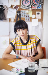 Asian designer painting in studio