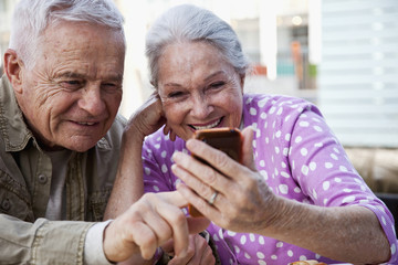 Senior Caucasian couple looking at cell phone