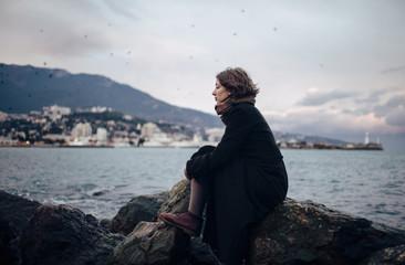 Woman in long coat sitting on rock in harbor