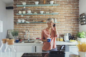 Woman in kitchen talking on smartphone