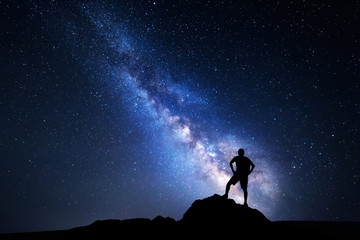 Milky Way. Night sky with stars and silhouette of a happy man with backpack. Space background
