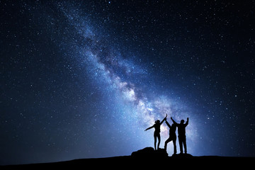 Night landscape with Milky Way and people. Sky with stars and silhouette of a happy family with raised-up arms.